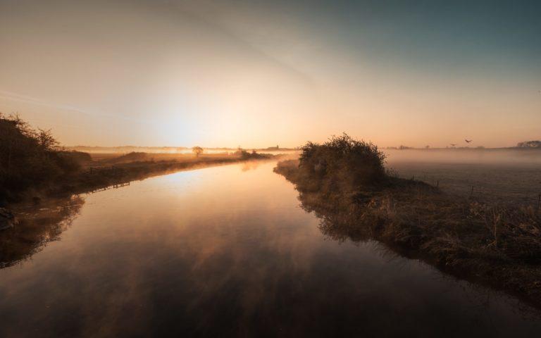 Mist hanging over river Nene in Northamptonshire at sunrise