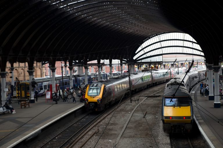 York, UK - August 05, 2013: York railway station where the platforms curve under the famous glass and iron curved arched roof. Train awaits departure to London. Some passengers are waiting train for departure.
