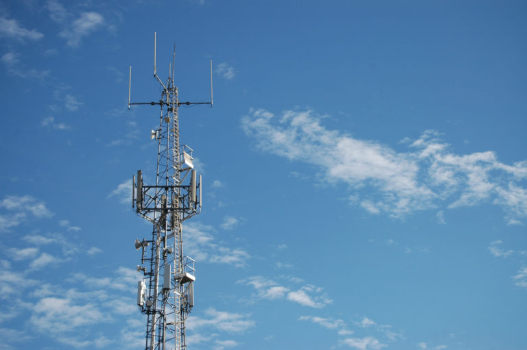 A Telecommunications tower against blue spring sky with a few wispy white clouds