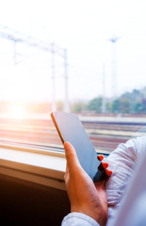 A person on a train holding a mobile phone